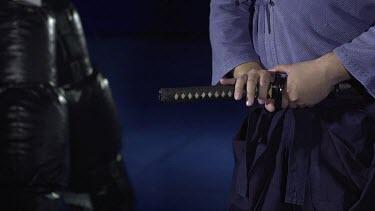 Man puting Sword back into holster_CU_Waist shot_3/4 angle