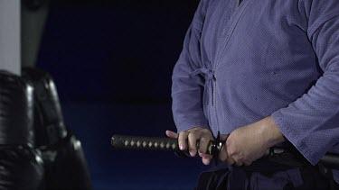 Man puting Sword back into holster_CU_Waist shot_3/4 angle_Slo Mo