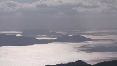 Kitan Straits; Japan. Wide shot of coastal landscape. Cliffs; ocean and distant islands all merge in same muted tones of shadow.
