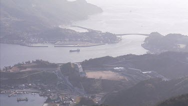 Kitan Straits; Japan. Wide shot high angle looking down at settlement on the coast. A ship passes through the narrow strait.