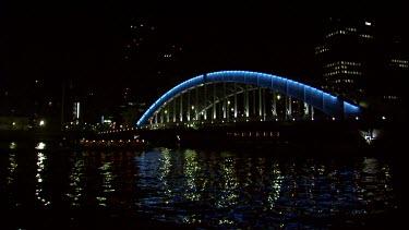 Eitaibashi bridge Tokyo at night. Lights of city reflect in the still black water.