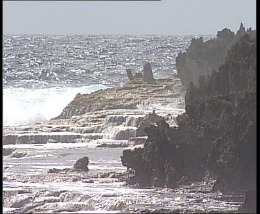 Waves crashing on coastline, cliffs and jagged rocks.