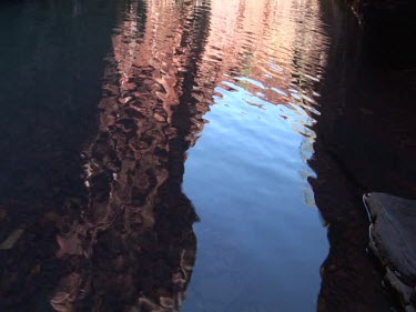 Ripples in a dark pool reflecting red rock of gorge cliffs