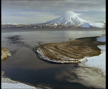Lake surrounded by ice and snow, with snow covered volcano in background.