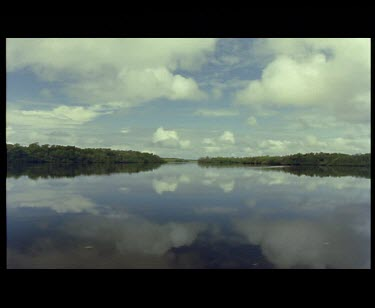 Tracking shot through channel in Mangrove covered islands at high water bright skies and reflections off the water.
