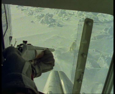 POV helicopter hunter aims rifle at arctic bear