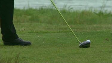 A Close up of a golfers club hitting the ball.