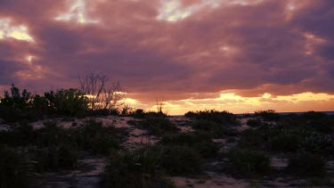 Clouds passing over a barren landscape. Day to night.