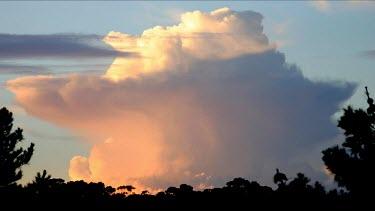 A spectular cloud formation expands as the sun sets to darkness. Comulo-nimbus cloud. Rain cloud.