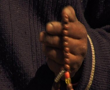 Close Up Of Hands Meditating Or Praying With Beads